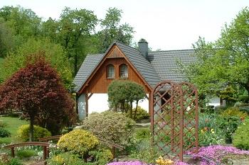Wypoczynek nieopodal Karpacza Sudecka Chatka Gruszków, widok na dom z ogródkiem i mostkiem Sudecka Chatka Gruszków,